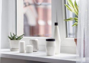 Decorative accessories standing on white windowsill in cozy home interior
